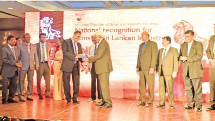 Dr. Indrajith Coomaraswamy presenting the special award to Mohideen Cader. Staff and officials look on