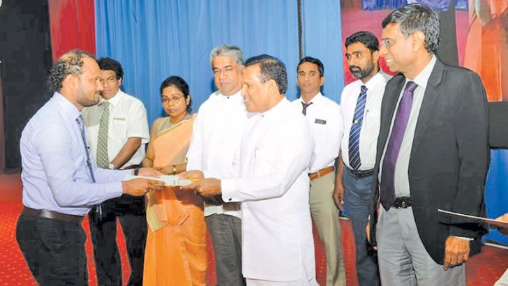 Health Minister Dr. Rajitha Senaratne hands over an appointment letter to an Ayurvedic doctor. Health Deputy Minister Fizal Kassim, Health Ministry Secretary Janaka Sugathadasa and others look on.