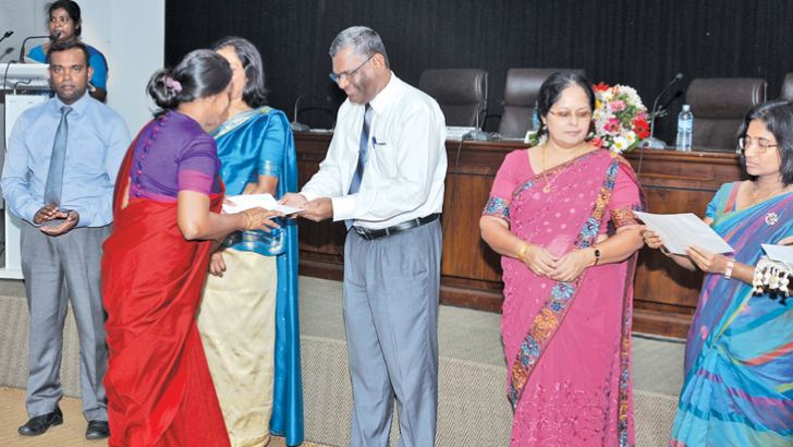 Secretary to the Public Administration and Management Ministry, J.J. Rathnasiri hands over an appointment letter to a newly recruited SLAS officer.