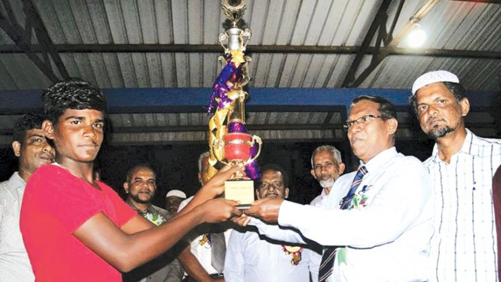 The captain of Rose House of Natpiddymunai Lafir Vidyalaya receiving the championship trophy from Kalmunai Zonal Education Director M.S.Abdul Jaleel. pix by  I. L. M. RIZAN.