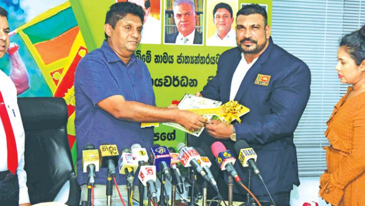 Lucien Anton Pushparaj receiving the deed of the house from the Housing and Construction Minister Sajith Premadasa. Ministry secretary R.M. Abeyratne is also present. Picture by Ashraff A. Samad
