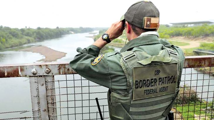 A U.S. Border Patrol agent scans the U.S.-Mexico border while on a bridge over the Rio Grande in Roma, Texas.