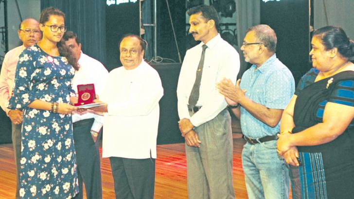 Minister S.B. Nawinne presents the third prize in the Drama Script competition (senior section) to M.I. Carson of the Colombo District. Picture by Wasitha Patabendige