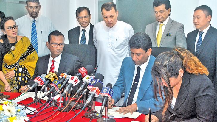 The MoU being signed. Minister Mahinda Samarasinghe and others look on. Picture by Siripala Halwala.