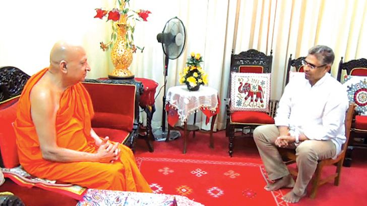 The Malwatte Prelate is in discussion with Minister Faizer Musthapha when he visited the Thera at his temple in Kandy yesterday. Picture by Gamini Ranasinghe.