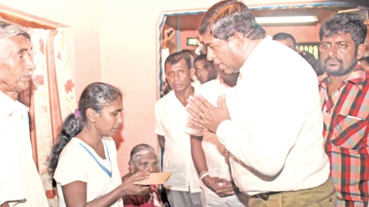 MP Ravi Karunanayake making financial donations to the affected families whose members died in the recent violence.