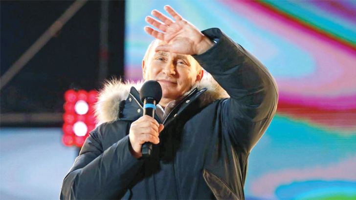 Russian President  Vladimir Putin  waves after speaking to  supporters near the  Kremlin in Moscow.