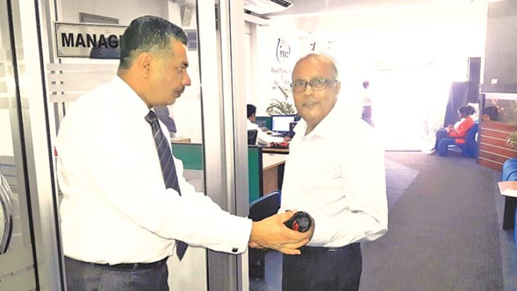 PLC Kandy branch Manager Asela Bandara, presenting a gift to a customer