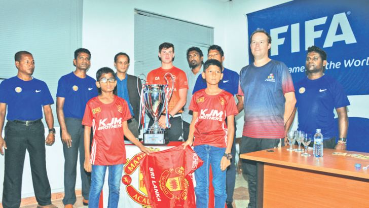 Two Young soccerites from Manchester Soccer Academy Jeremy Augustine and Himayath Akram after unveiling the International Independence Cup at the launching ceremony held at the Football Federation of Sri Lanka with Officials of Academy Monday.
