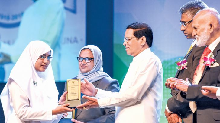 President Maithripala Sirisena presenting an award to a student at the centenary celebration meeting of Fathima Muslim Ladies' College, Colombo at the Nelum Pokuna Theatre yesterday.  Picture by Udesh Gunarathna, President's Media Division. (Story on page 12)