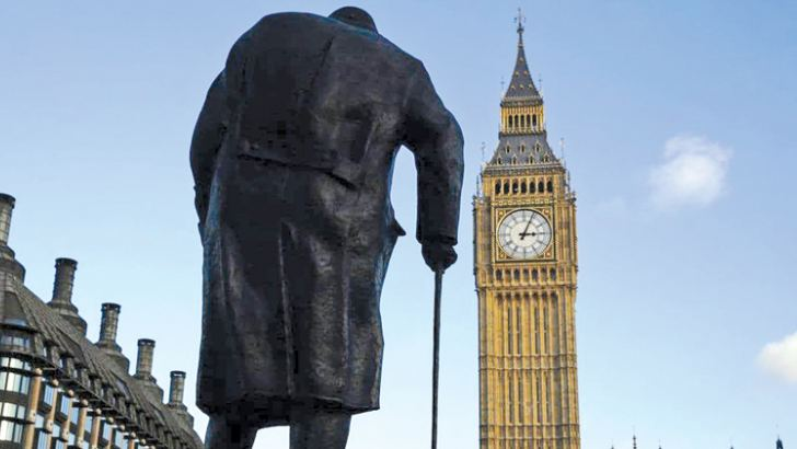 A statue of former British Prime Minister Winston Churchill is silhouetted in front of the Houses of Parliament in London in 2015.