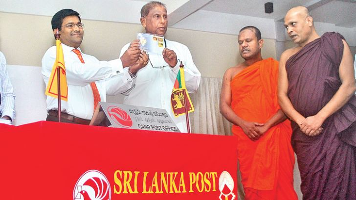 Minister Gamini Jayawickrama Perera launching the First Day Cover and stamps.  Picture by Siripala Halwala.