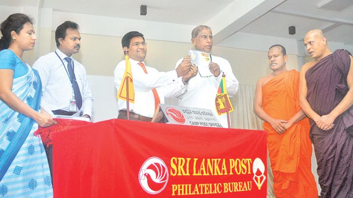 The new three stamps and the first day cover are being presented to the Buddha Sasana, Sustainable Development and Wildlife Minister Gamini Jayawickrama Perera by Post and Postal Services Ministry Secretary R. M. D. B. Meegasmulla. Ven. Ruwanwella Dammaratana Thera, Buddha Sasana Ministry Secretary Chandrapema Gamage, Buddhist Affairs Commissioner General Nimal Kotawelagedara are present. Picture by Siripala Halwala