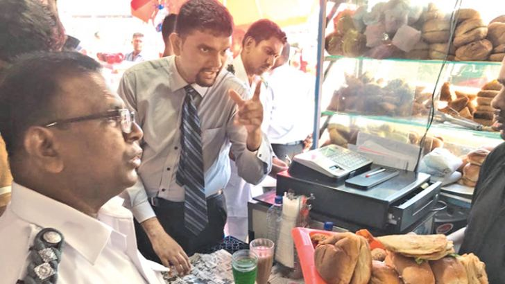 Public Health Inspectors conducting a raid on one of the eateries in Colombo Fort yesterday.