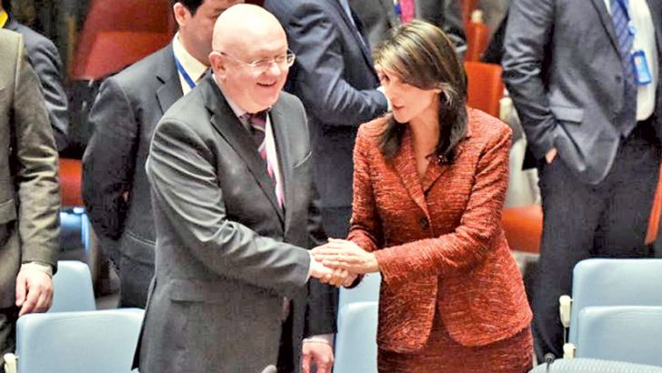 US Ambassador to the United Nations Nikki Haley shakes hands with her Russian counterpart Vassily Nebenzia during a UN Security Council meeting.- AFP