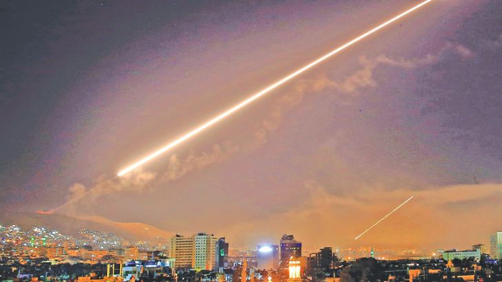 The Damascus sky lights up with surface-to-air missile fire as a U.S.-led attack targeted different parts of the Syrian capital early Saturday, April 14, 2018.
