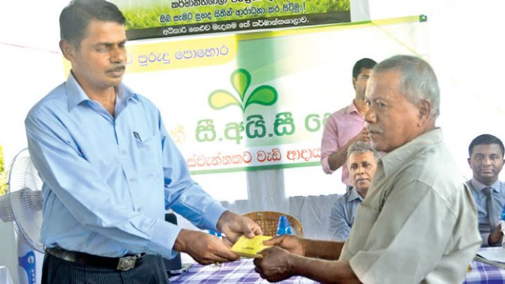 Akuressa 20180401 - Extention Manager of the smallholders factories PLC Dr. Lalith Amaratunga gifting a bonus packet to a tea small holder.