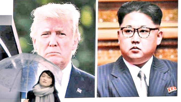 A woman walks by a huge screen showing U.S. President Donald Trump and North Korea's leader Kim Jong Un, in Tokyo.