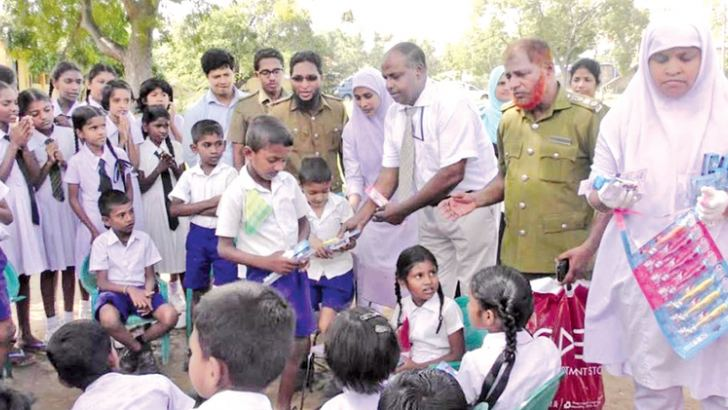 Dr. Latheef distributes toothpaste and toothbrushes.