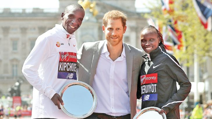 Britain's Prince Harry (C) poses with elite men's race winner Kenya's Eliud Kipchoge (L) and elite women's race winner Kenya's Vivian Cheruiyot during the trophy ceremony of the 2018 London Marathon in central London on Sunday. - AFP