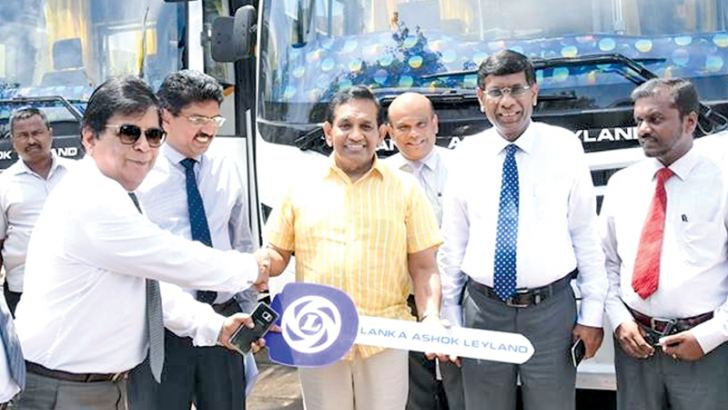 Minister Dr. Rajitha Senaratne symbolically handing over the buses.