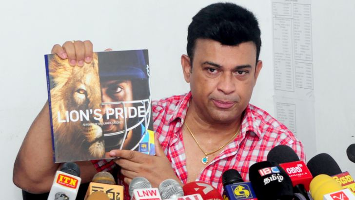 Deputy Minister of Social Empowerment, Welfare and Kandyan Heritage, Ranjan Ramanayake holds up a copy of a book titled 'Lions Pride' at a press conference held at Madiwela yesterday. The Minister alleged SLC had wasted Rs. 1.2 million in publishing this book. Pic by Wasitha Patabandige