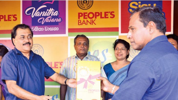 People's Bank Senior Deputy General Manager (Banking Operations) Bonniface Silva presenting a token gift to Commander of Southern Naval Area, Rear Admiral S.M.D.K. Samaraweera as a mark of signifying the New Year transaction.