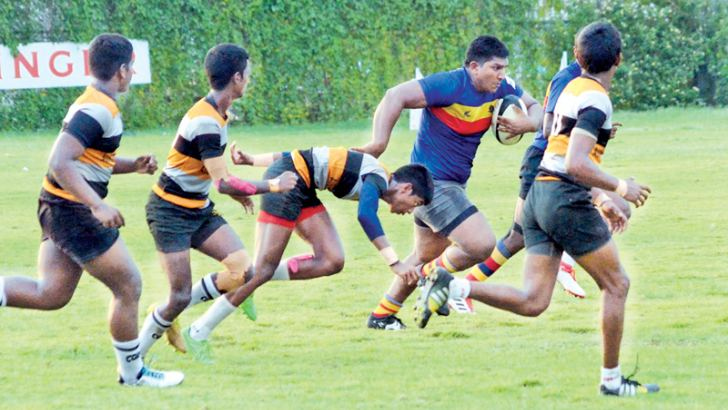 A Thurstan College player on his way for a try score, evading Mahanama defenders.