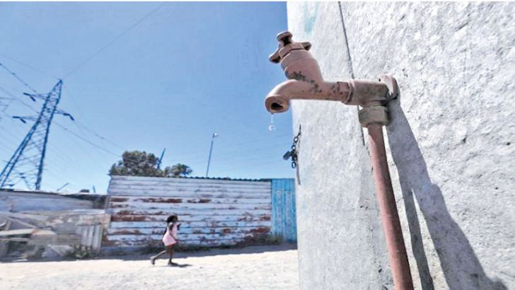Residents walk past a leaking communal tap in Khayelitsha township, near Cape Town, South Africa.