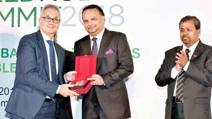 Plantation Industries Minister Navin Dissanayake presenting a token to the Secretary General, International Rubber Study Group Salvatore Pinizzotto. Secretary to the Minister J.A. Ranjith is also in the picture.