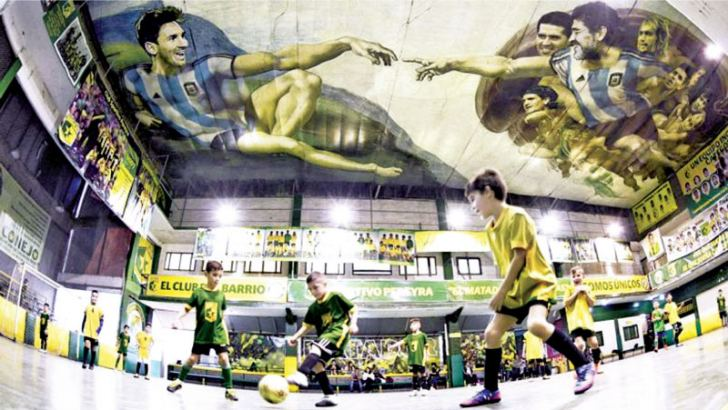 7eb7e846bb Boys play soccer as images of Lionel Messi and Diego Maradona are seen  depicted on the