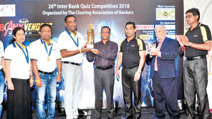Winners – The captain of the HNB 'A' Team receives the trophy from the main sponsor and chief guest,  Senarath Bandara, the General Manager and CEO of Bank of Ceylon. M. Razak Deen, the President of CAB, Ravi Molligoda, the Quiz Master and Janak Palugaswewa, the Secretary of CAB are also present.