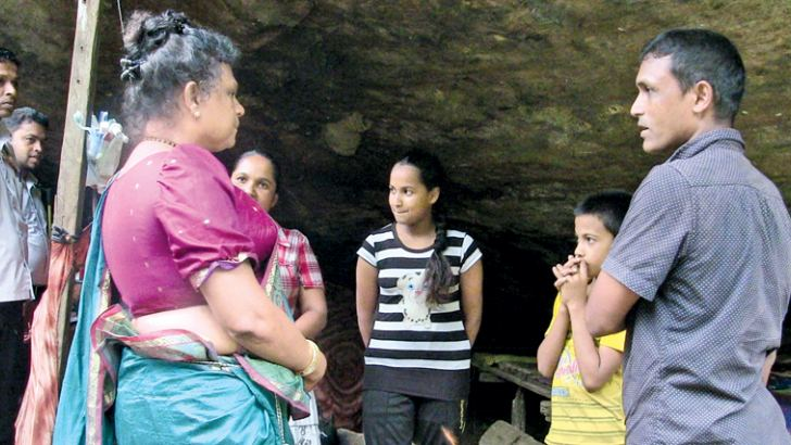 Sabaragamuwa Provincial Governor Niluka Ekanayaka in conversation with family members living inside a cave.