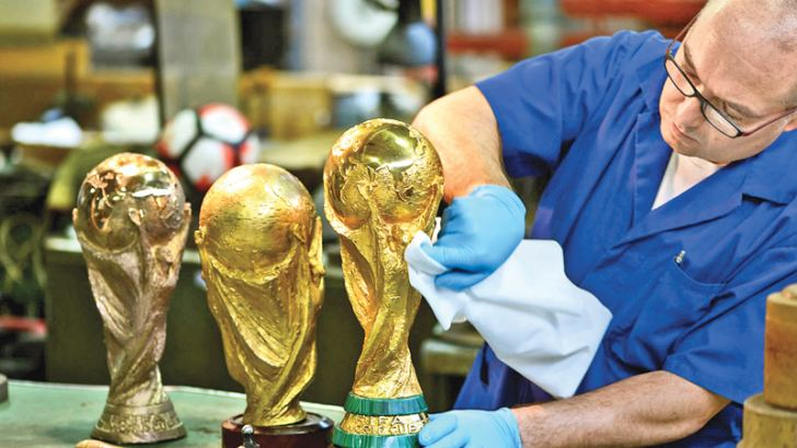 An GDE Bertoni artisan operator cleans a replica of the World Cup trophy. AFP