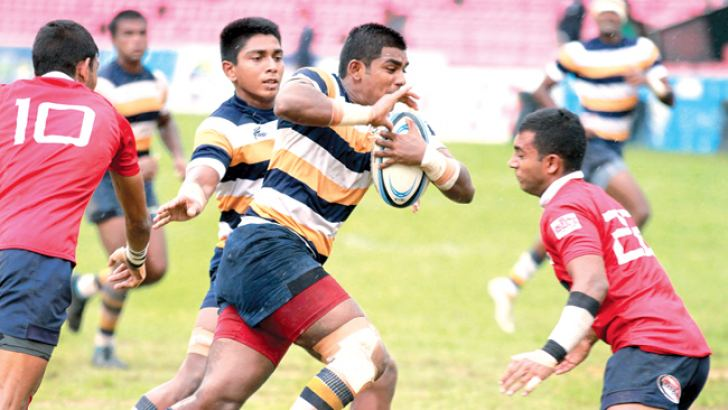 Peterite second row forward Nizran Nillar  makes a break supported by flanker Themal Fernando with Kingswoodian Asiri Seneviratne (No.10) making a vain bid to foil him. In their Singer 'A' Division League Rugby match played at Havelock, Park yesterday which St. Peter's won 20-10. Picture by Samantha Weerasiri