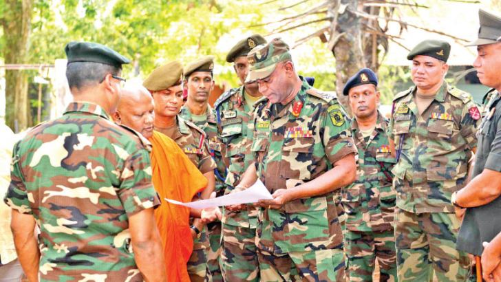 Army Commander Lieutenant General Mahesh Senanayake in consultation with a Buddhist prelate over a proposed project.
