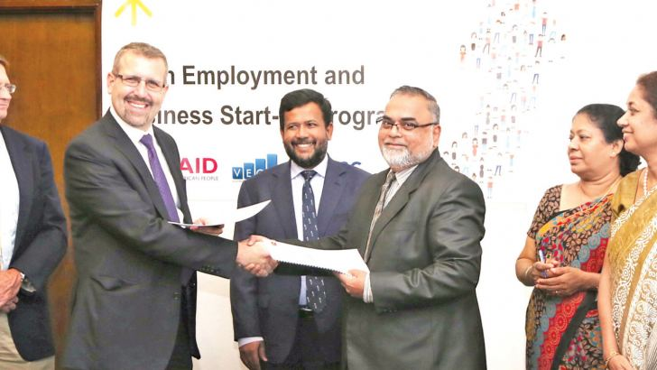 Charles Conconi (YouLead Project Director -second from left) and  CEO-Lanka Sathosa Dr Mohamed Faraz (fourth from left) exchange MoU documents in the presence of the Minister  Bathiudeen (third from left) joined by Brian Wittnebel (Acting  Director of USAID Economic Growth Office-far left), Additional Secretary  of Ministry of Industry and Commerce Sheitha Senaratne (second from  right) and Senior Advisor to Minister Bathiudeen, Himali Jinadasa (far  right).