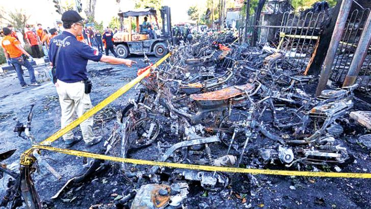 This file photo taken on May 13, 2018 shows a man looking at burnt-out motorcycles following a bomb blast outside the Surabaya Centre Pentecostal Church (Surabaya Gereja Pantekosta Pusat) in Surabaya, East Java Province. - AFP
