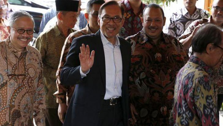 Malaysian politician Anwar Ibrahim (centre) waves to journalists arriving at former Indonesian President BJ. Habibie residence in Jakarta on May 20. - AFP