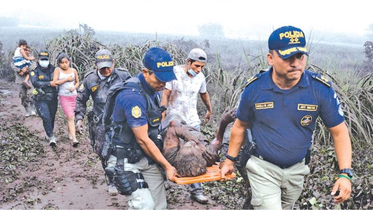 Police officers carry a wounded man after Guatemala's Fuego volcano eruption. - AFP