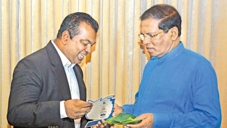 Dr. Ukwatte handing over a token to President Maithripala Sirisena who was the Chief Guest at investment conference hosted by Property Club in Colombo. Picture by Sudath Malaweera