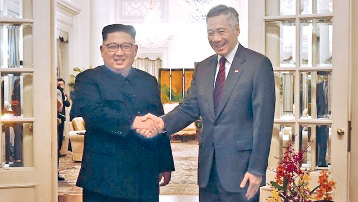 Singaporean Prime Minister Lee Hsien Loong, (R), greats North Korean leader Kim Jong Un in Singapore on June 10.