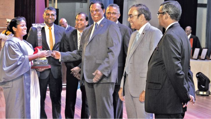 Chief Guest Minister, John Amaratunga, Secretary to the Ministry of Tourism Development, Esala Weerakoon, Chairman, Sri Lanka Institute of Tourism and Hotel Management, Sunil Dissanayake presenting an award to one of the students. Picture by Saliya Rupaisnghe