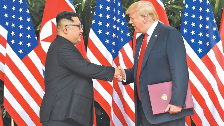 North Korean leader Kim Jong Un shakes hands with US President Donald Trump after a signing ceremony at the end of their historic US-North Korea summit, at the Capella Hotel on Sentosa island in Singapore yesterday. - AFP