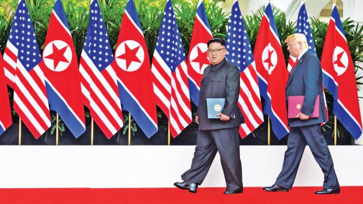 US President Donald Trump (R) walks out with North Korea's leader Kim Jong Un after the end of their historic summit in Singapore on Tuesday.