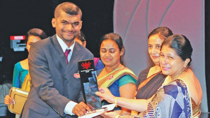 ANCL employee Sanjeewa Ruwan Fernando, who has donated blood for more than 65 times, received an award from a Health Ministry official at the ceremony. Picture by Wasitha Patabendige
