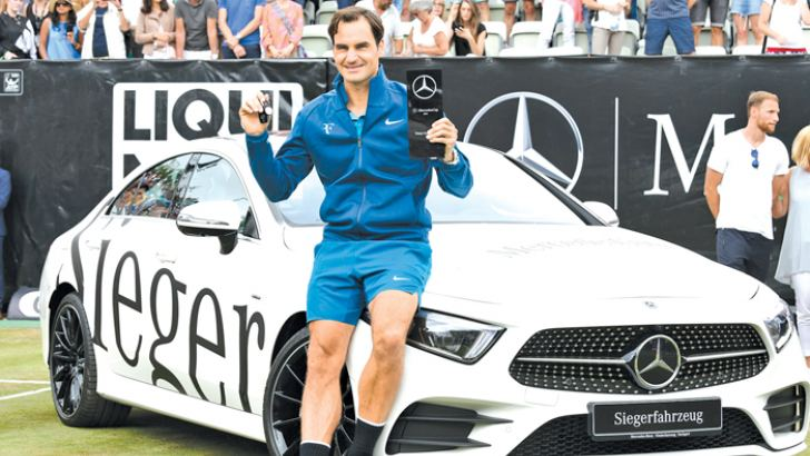 Switzerland's Roger Federer poses with the trophy in front of the winner's car, a Mercedes-Benz E450, after he won against Canada's Milos Raonic in the final match at the ATP Mercedes Cup tennis tournament in Stuttgart, southwestern Germany, on June 17.  AFP