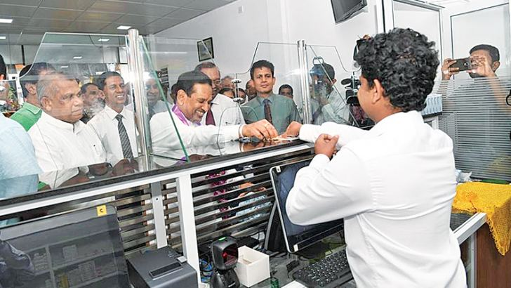 Health Minister Dr. Rajitha Senaratne makes the first purchase of drugs, while Law and Order Minister Ranjith Madduma Bandara and others look on.