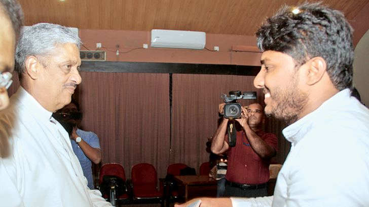 Tharaka Umayanga Dilshan presents a copy of his book to Minister Sarath Fonseka. Picture by Roshan Pitipana