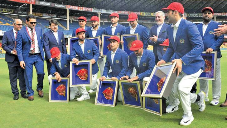 Afghanistan cricket team members pose for a group photograph prior to the start of the one-off cricket Test match against India at the M. Chinnaswamy Stadium in Bangalore on June 14. - AFP
